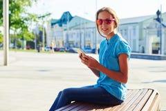 Портрет темн-с волосами девочка-подростка сидя с smartphone дальше Стоковые Изображения RF