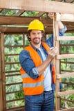 Портрет тимберса рабочий-строителя измеряя Стоковая Фотография