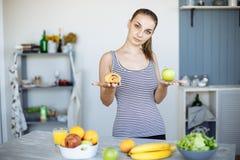 Портрет тонкой привлекательной женщины делая выбор между Яблоком и сладостной плюшкой, пробуя сопротивляться заманчивости стоковое изображение rf