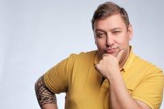 Портрет тучного кавказского человека в желтой футболке представляя в студии на серой предпосылке стоковые изображения