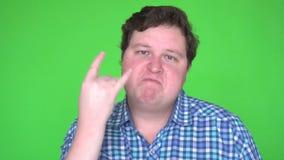 Портрет тучного коромысла человека показывать с рукой и смотря камеру против зеленой предпосылки видеоматериал
