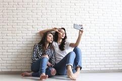 Портрет 2 тысячелетних женщин, околпачивая вокруг перед передвижной камерой smartphone Брайн наблюдал модельные девушки с длинным Стоковая Фотография RF