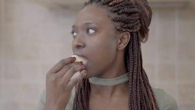 Портрет уверенной Афро-американской молодой усмехаясь женщины сдерживая вкусный кусок яблока и усмехаться сток-видео