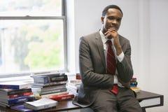 Портрет уверенно Афро-американского бизнесмена сидя на столе офиса Стоковая Фотография