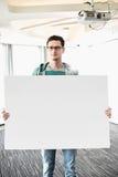 Портрет уверенно бизнесмена держа пустую доску в творческом офисе Стоковые Фотографии RF