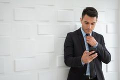 Портрет уверенно бизнесмена использует сотовый телефон стоковая фотография