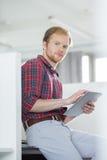 Портрет уверенно бизнесмена используя ПК таблетки в творческом офисе Стоковое фото RF