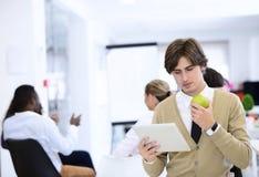 Портрет уверенно бизнесмена используя цифровую таблетку пока коллега в предпосылке Стоковые Фото