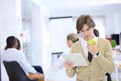 Портрет уверенно бизнесмена используя цифровую таблетку пока коллега в предпосылке Стоковое Изображение