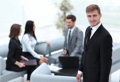 Портрет уверенно бизнесмена на предпосылке офиса Стоковое фото RF