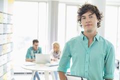 Портрет уверенно бизнесмена при коллеги работая в предпосылке на творческом офисе Стоковая Фотография RF