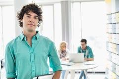 Портрет уверенно бизнесмена при коллеги работая в предпосылке на творческом офисе Стоковое Изображение RF