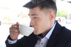 Портрет уверенно бизнесмена сидя на стенде и выпивая кофе outdoors Стоковая Фотография