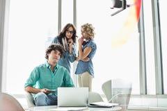 Портрет уверенно бизнесмена сидя на таблице при женские коллеги беседуя в предпосылке Стоковое Изображение RF