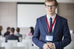 Портрет уверенно бизнесмена стоя на зале семинара при коллеги сидя в предпосылке Стоковое фото RF