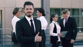 Портрет уверенно бизнесмена стоя outdoors с его коллегами и показывая он доволен видеоматериал