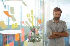 Портрет уверенно бизнесмена с оружиями пересек готовя стратегию на стекле на офис Стоковая Фотография RF
