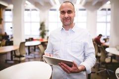 Портрет уверенно бизнесмена с цифровой таблеткой на творческом офисе Стоковое Фото