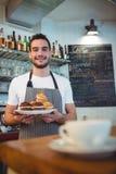 Портрет уверенно кельнера с пирожными на кофейне Стоковое Изображение RF