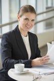Портрет уверенно коммерсантки при документы сидя на кафе офиса Стоковая Фотография