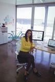 Портрет уверенно коммерсантки сидя на столе офиса Стоковые Фото