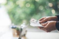 Портрет уверенно молодого азиатского бизнесмена смотря к правильной позиции Руки подсчитывая банкноты доллара, стоковая фотография