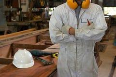 Портрет уверенно молодого работника в белой равномерной руке ` s креста одного над комодом в мастерской плотничества Стоковые Изображения RF