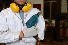 Портрет уверенно молодого работника с электрическим сверлильным аппаратом безопасности равномерным держа в мастерской плотничеств Стоковые Фото