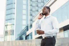 Портрет уверенно молодого черного бизнесмена говоря на сотовом телефоне Стоковые Изображения