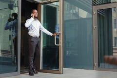 Портрет уверенно молодого черного бизнесмена говоря на сотовом телефоне Стоковое Изображение RF