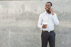 Портрет уверенно молодого черного бизнесмена говоря на сотовом телефоне Стоковое Изображение