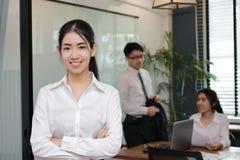 Портрет уверенно молодой азиатской бизнес-леди стоя в офисе с коллегами в предпосылке конференц-зала стоковое изображение