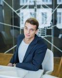 Портрет уверенно молодого бизнесмена сидя на столе переговоров Стоковые Изображения