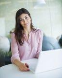 Портрет уверенно молодой коммерсантки используя компьтер-книжку на таблице офиса Стоковые Изображения RF
