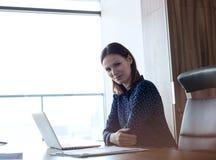 Портрет уверенно молодой коммерсантки с компьтер-книжкой на столе в офисе Стоковое фото RF