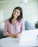 Портрет уверенно молодой коммерсантки с компьтер-книжкой на таблице офиса Стоковое Изображение RF