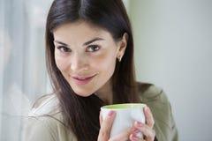 Портрет уверенно молодой коммерсантки с кофейной чашкой в офисе Стоковые Фотографии RF