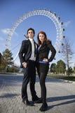 Портрет уверенно молодых пар дела стоя совместно против глаза Лондона, Лондона, Великобритании Стоковое Изображение RF