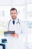 Портрет уверенно мужского доктора с доской сзажимом для бумаги Стоковая Фотография