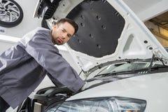 Портрет уверенно мужского работника ремонта ремонтируя двигатель автомобиля в ремонтной мастерской Стоковые Изображения RF