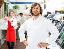 Портрет уверенно мясника стоя на магазине стоковые изображения