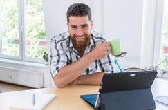 Портрет уверенно работающий на самого себя молодого человека сидя на столе Стоковое Изображение
