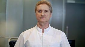 Портрет уверенно старшего доктора стоя на больнице пока смотрящ камеру Стоковые Изображения