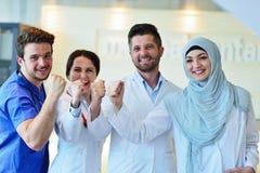 Портрет уверенно счастливой группы в составе доктора стоя на медицинском офисе Стоковые Фото