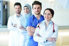 Портрет уверенно счастливой группы в составе доктора стоя на медицинском офисе Стоковое Фото