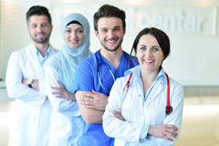 Портрет уверенно счастливой группы в составе доктора стоя на медицинском офисе Стоковое фото RF