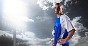 Портрет уверенно футболиста с рукой на бедре против неба Стоковое Изображение