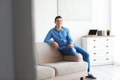 Портрет уверенно человека на софе стоковое изображение rf