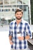 Портрет уверенно человека смотря отсутствующий пока держащ устранимый ПК чашки и таблетки в городе Стоковые Изображения RF