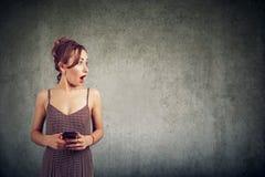 Портрет удивленной женщины держа мобильный телефон и смотря прочь на космосе экземпляра Стоковое Изображение